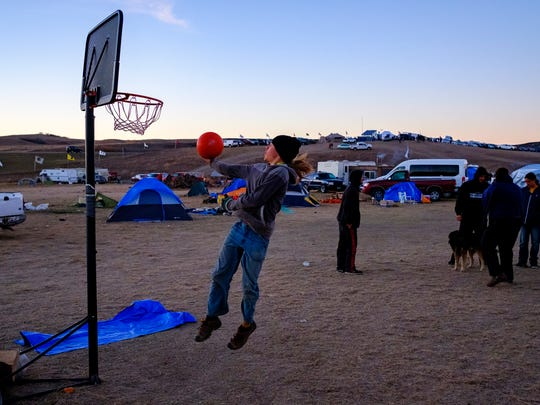 Connor Manson, 16, plays basketball as other teenagers play hacky sack at the Oceti Sakowin campground near Cannon Ball, N.D. on Friday, Nov. 11, 2016.