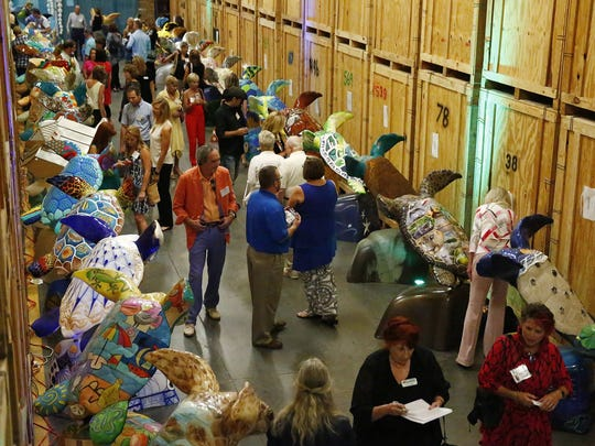 Patrons fill a warehouse row Wednesday, Nov. 4, 2015, at William C. Huff Companies in Naples, before the turtles were shipped to public locations around the county where people could enjoy the turtles before they were auctioned off to support three local organizations.