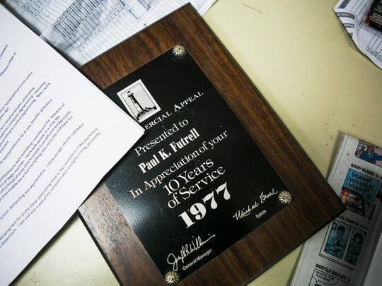 A 1977 plaque commemorating Paul Futrell's 10-year work anniversary rests on a desk in the mail room on Thursday.