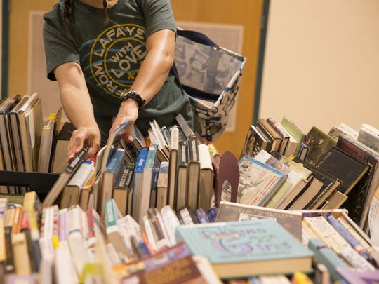 A shopper looks through books at the Friends of the Library September sale.