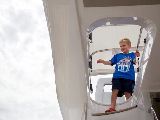 Jack Paterson, 8, of Naples, climbs down from the deck of a $1.2 million Azimut 45 Fly displayed by MarineMix at the Naples Boat Show Downtown at the Naples City Dock on Oct. 4, 2014.