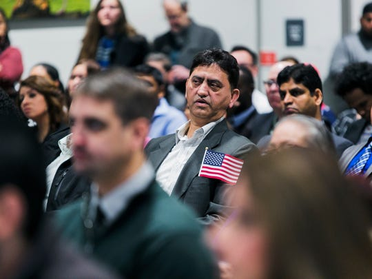 Ghias Mufti, 52, of Pakistan, sits quietly in his seat with his American flag tucked in his coat pocket prior to the start of the Naturalization Ceremony at the Benjamin L. Hooks Central Library in East Memphis on Friday. Mufti was one of 99 people to become an American citizen after taking the Oath of Allegiance during the ceremony.