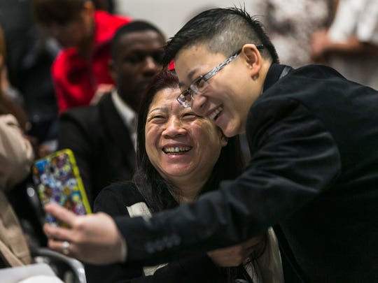 Xiao Zhang, 56, of China, has her portrait taken with her son, Denny Law, 31, prior to the start of the Naturalization Ceremony at the Benjamin L. Hooks Central Library in East Memphis on Friday. Law's parents, Xiao Zhang and Zhi Luo, 56, became American citizens after taking the Oath of Allegiance with 97 others during the ceremony.