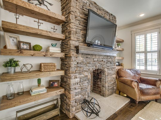 Justin and Rachel Holder had a stone gas fireplace installed as well as floating shelves made of reclaimed wood. The Holders also chose to keep the original single-pane windows, so the custom plantation shutters help with energy efficiency.