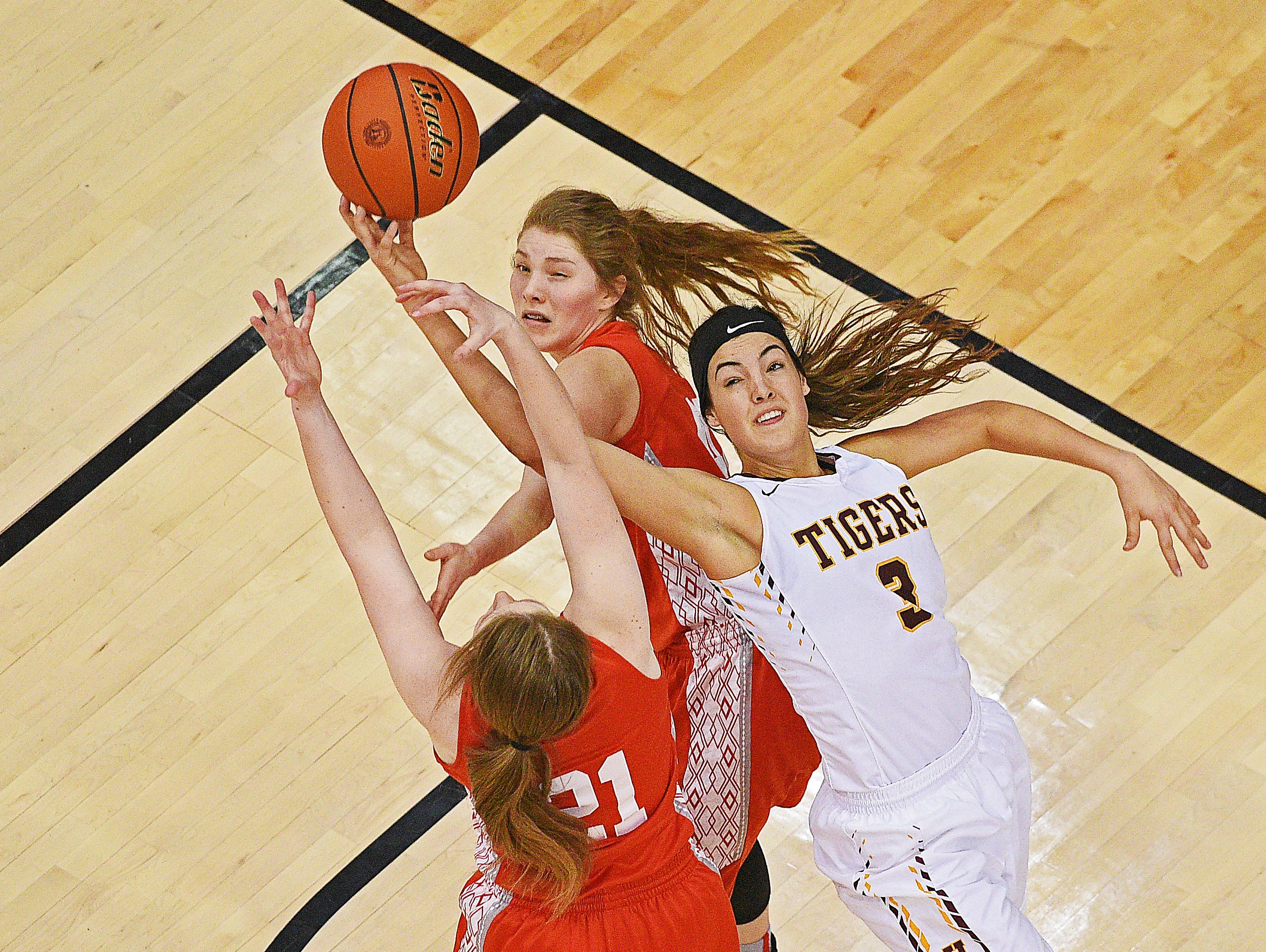Harrisburg's Sami Slaughter (3) reaches for a rebound over Rapid City Central's Juneau Jones (42) and Abby Johnson (21) during a 2017 SDHSAA Class AA State Girls Basketball semifinal game Friday, March 17, 2017, at Rushmore Plaza Civic Center in Rapid City. Harrisburg beat Rapid City Central 49-44, and will play in Saturday's final.