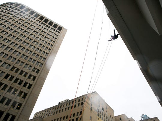 "Melissa Renzi waves to her son J.J. as she rappels down 17 stories (222 feet) at the TD Bank building in downtown Wilmington as part of ""Over the Edge"" to raise money and awareness for Special Olympics Delaware."