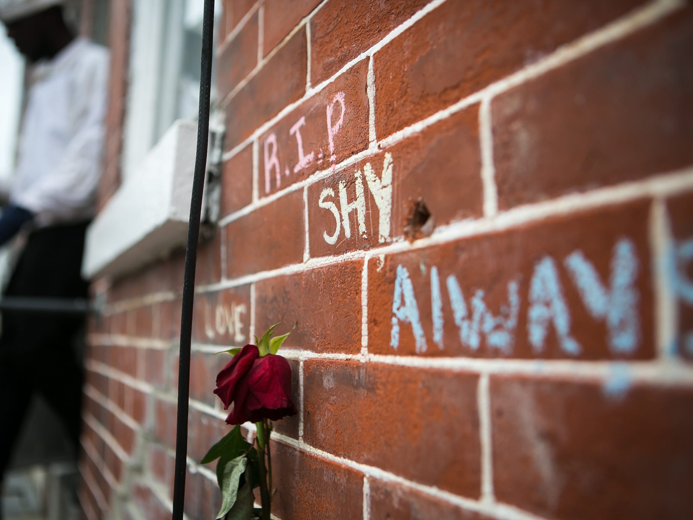 A rose and messages are left on the front brick wall