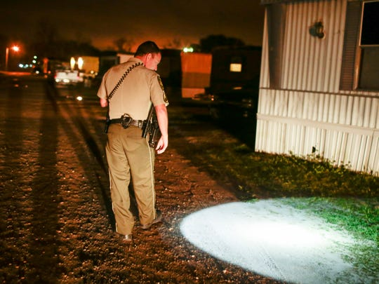Lafayette Parish Sheriff's Sgt. Clay Carter searches a trailer park for clues after a battery call late Friday, February 17, 2017.