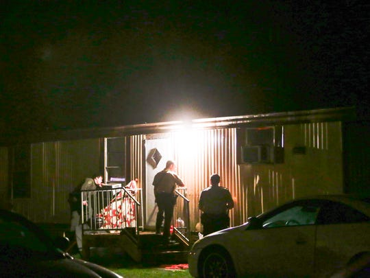 Lafayette Parish Sheriff's deputies approach a trailer where marijuana smoke was smelt outside by deputies on an un-related call- prompting an in vestigatiion and search warrant- in the early hours of Saturday morning, February 18, 2017.