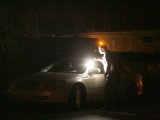 A Lafayette Parish Sheriff's deputy looks into a car