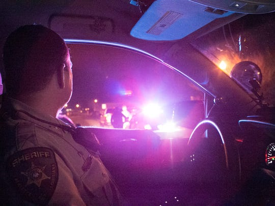 Lafayette Parish Sheriff's Sgt. Clay Carter looks over deputies who have pulled over a driver in the early hours of Saturday morning, February 18, 2017.