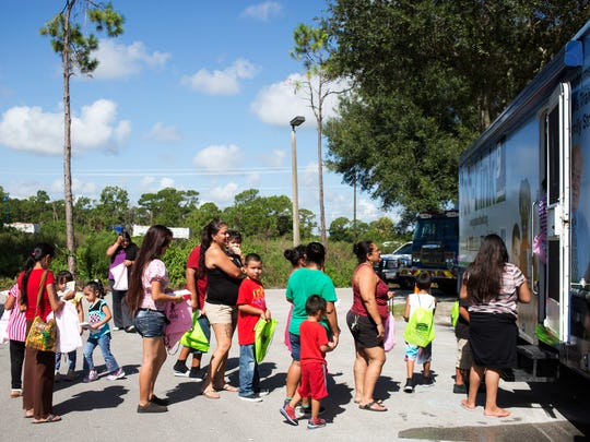 Attendees line up outside Goodwill Industries of Southwest Florida's Mobile Job-Link RV at Celebrate Immokalee on Aug. 11, 2015. (Carolina Hidalgo/Staff)