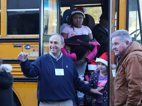 Weigel's CEO Bill Weigel (blue sweater) directs children as they get off the bus to enter Kmart for their $150 shopping spree last season.