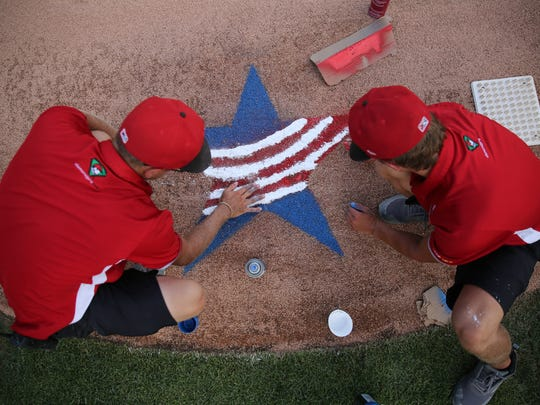 Indianapolis Indians grounds crew prepare a Fourth of July decoration and Victory Field