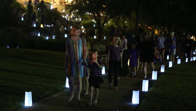 Attendees walk among luminary bags placed around the San Angelo Visitors Center during the West Texas Counseling and Guidance's 2nd annual Shine a Light event Saturday, Sept. 9, 2017.
