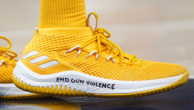 """Utah Jazz guard Donovan Mitchell, a former University of Louisville player, wears a shoe with """"End gun violence"""" written on it, during the second half of the team's NBA basketball game against the Phoenix Suns on Wednesday, Feb. 14, 2018, in Salt Lake City."""