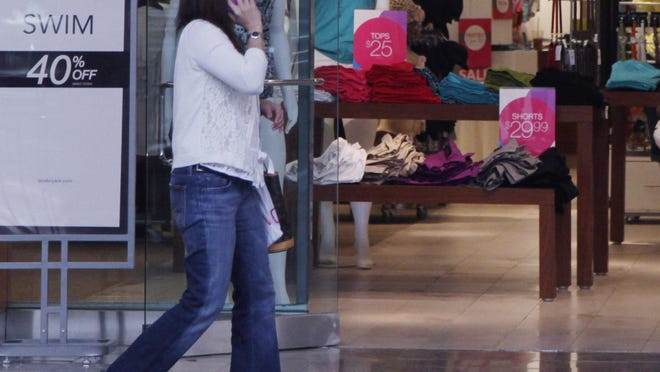 FILE - In this June 15, 2012 file photo, a woman walks past a Lane Bryant store in San Jose, Calif. The operator of Lane Bryant, Ann Taylor and Catherines filed for Chapter 11 bankruptcy on Thursday, July 23, 2020, the latest retailer to do so during the pandemic. Mahwah, New Jersey-based Ascena Retail Group Inc., which operates nearly 3,000 stores mostly at malls, has been dragged down by debt and weak sales for years.