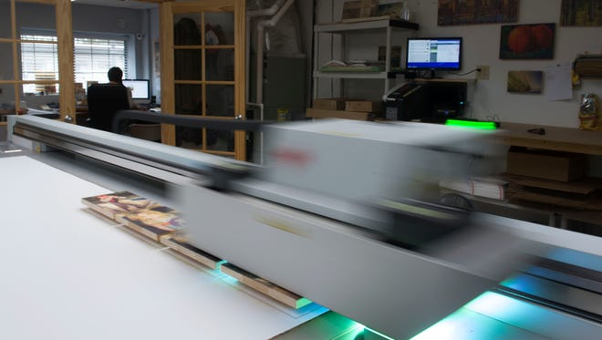The printer glides over multiple pieces of wood as Wyatt Harrison works in the background.