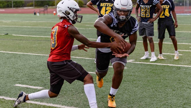 Battle quarterback Khaleel Dampier (3) hands off to Rickie Dunn during preseason practice Aug. 11 at Battle High School.
