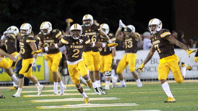Wyoming players celebrate a late-fourth-quarter safety that resulted in the winning points against Boise State during an NCAA college football game Saturday, Oct. 29, 2016, in Laramie, Wyo. (Joe Jaszewski/Idaho Statesman via AP)
