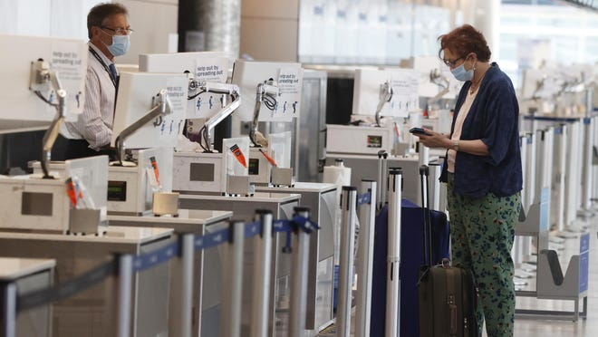 A passenger checks in with an agent at the United Airlines ticketing counter in the main terminal of Denver International Airport on May 22.