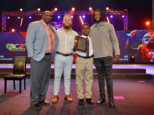 Former Clemson football players Mike Williams, far right, and Ben Boulware, middle left, pose for a photo with Greer Middle School Principal Dan Bruce, far left, and Vincent Bush, The Greenville News Coaches 4 Character Award winner,  during the Coaches 4 Character event Monday, March 27, 2017, at Redemption World Outreach Center.