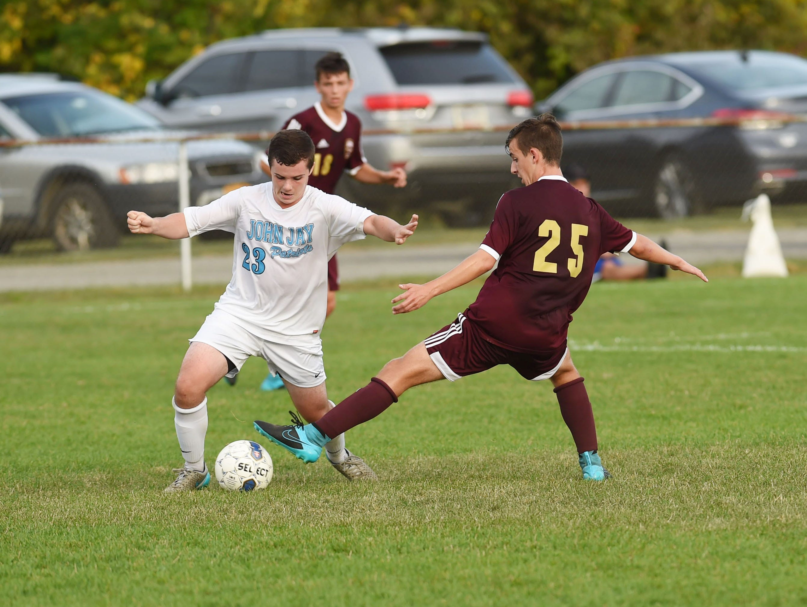 John Jay's Kevin Turi, left, tries to keep the ball away from Arlington's Paul Makaj, right, during Monday's game.