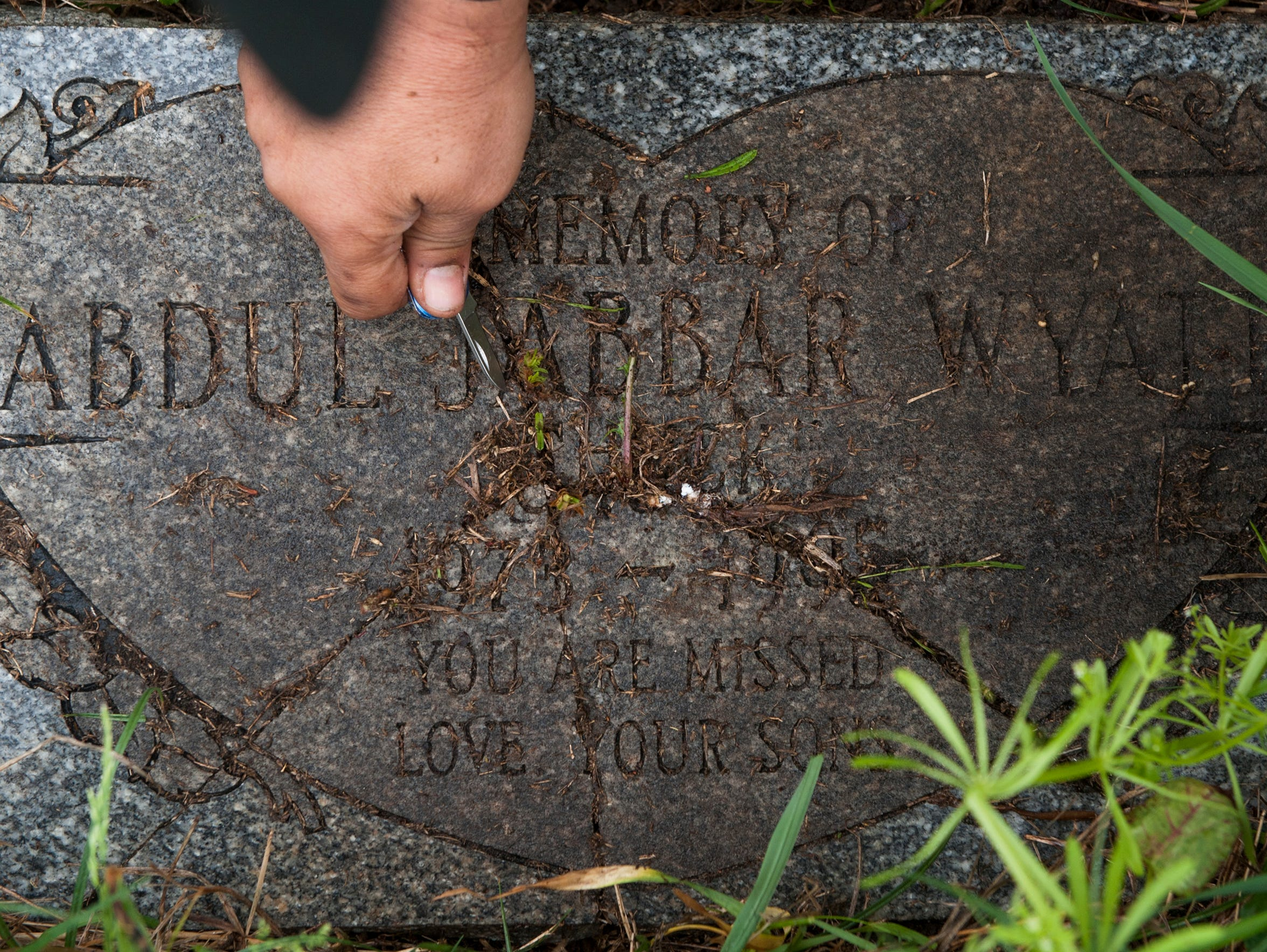 Donald Wyatt clears weeds from the gravestone of his