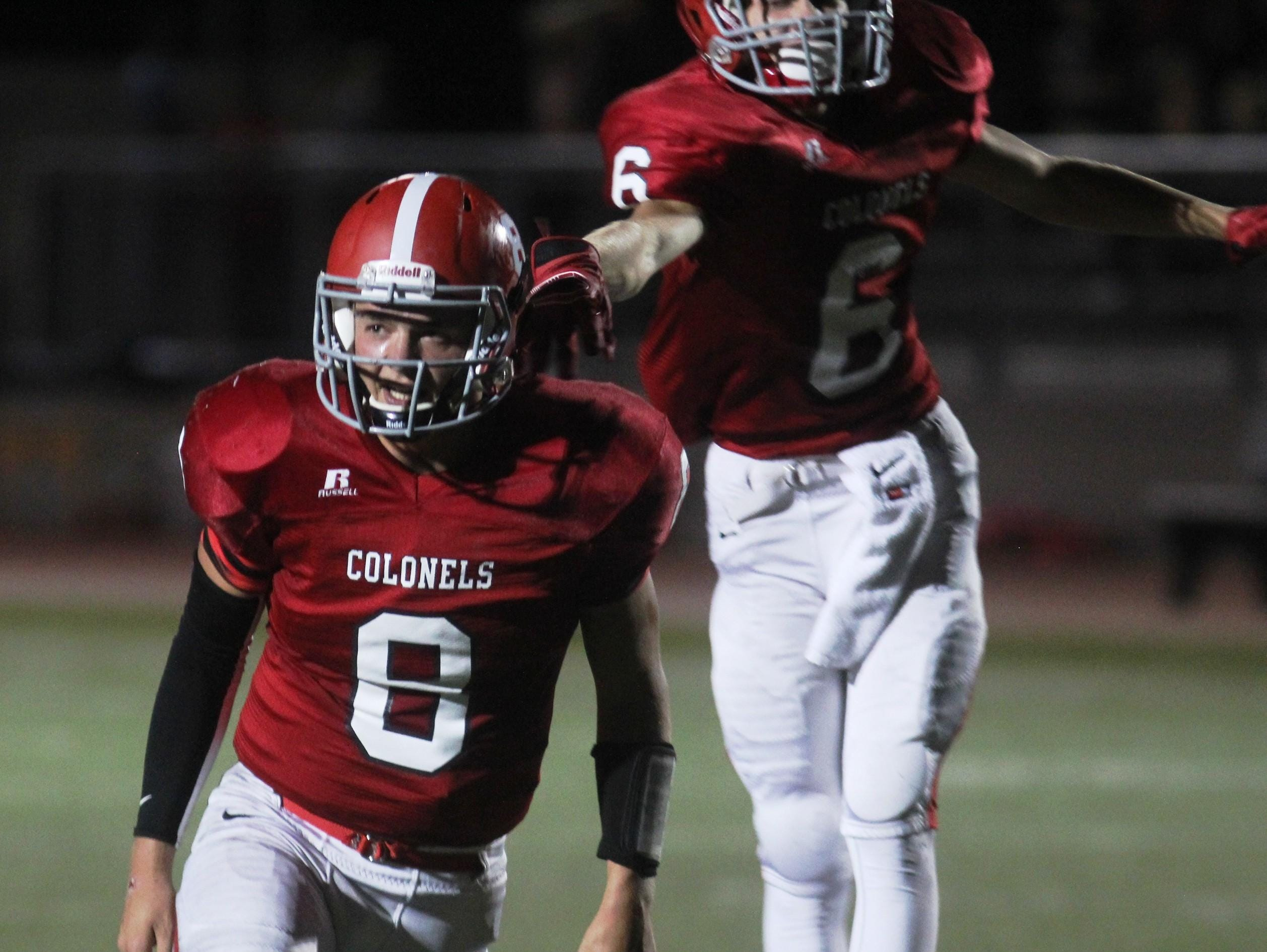 Dixie Heights' Gunther Faeth, front, gestures to the crowd after his second touchdown run of the game against Boone County.