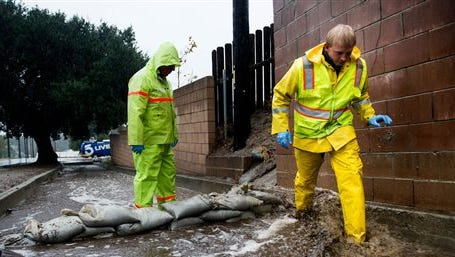 Glendora work crews clear debris and mudflows in the storm drain below the Colby Fire burn area in 1000 block of N Lorain Avenue in Glendora, Calif. on Tuesday. Heavy rain from a powerful Pacific storm swept through California on Tuesday, providing some relief from a three-year drought.