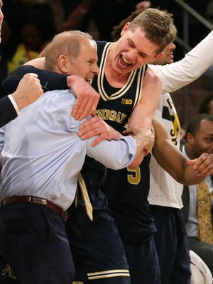 Coach John Beilein and his Michigan Wolverines celebrate their Big Ten tournament title on March 4, 2018.