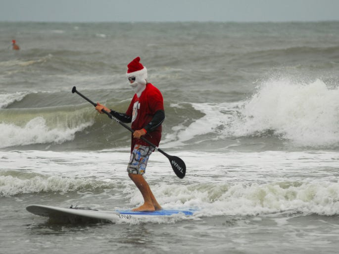 "Santa surfs toward shore on a paddleboard Dec. 24 in Cocoa Beach, Fla. The ""Surfin' Santas 2013 Christmas in the Sand"" event featured more than 200 surfing Santas, elves, snowmen and other Christmas characters."