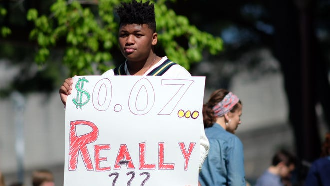 "A student at L&N STEM Academy holds a sign with ""$0.07,"" representing each student's worth based on NRA donations to Tennessee politicians, Friday, April 20, 2018."