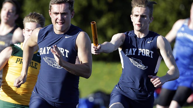 Bay Port's Jacob Isaac, right, hands the baton to teammate Joshua Jennerjohn on the final turn of the 400-meter relay at the FRCC boys relay meet at De Pere on Monday.