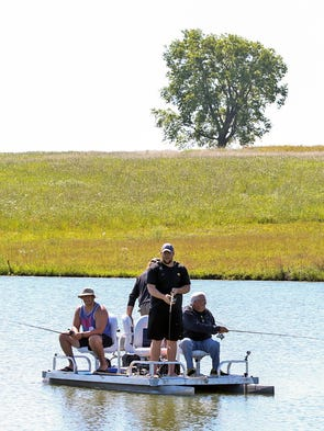 Iowa Hawkeye offensive lineman Brandon Scherff, center, fishes with teammates at a farm pond outside Williamsburg on Wednesday, July 16, 2014, in eastern Iowa.