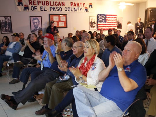 Mark Dunham, right, and Blanca Trout, center, clap while watching President Donald Trump's State of the Union address at El Paso County Republican Party headquarters.