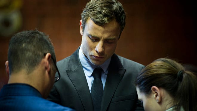 In this Monday, Aug. 19, 2013, file photo,  Oscar Pistorius cries as he prays with his sister Aimee, right, and brother Carl in the magistrates court in Pretoria, South Africa.
