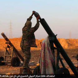 Islamic State militants prepare to fire a mortar to shell toward Syrian government forces positions at Tal Arn in Aleppo province, Syria.