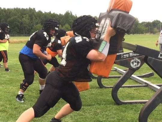 A Marshfield lineman hits the blocking sled during a recent team practice.