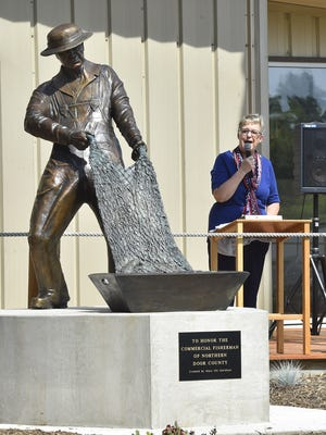 Mary Ott Davidson of Saucier, Mississippi, who designed the bronze sculpture in front of Death's Door Maritime Museum, 12724 W. Wisconsin Bay Road, Gills Rock, helped to dedicate the monument on Wednesday.