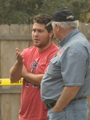 At top: Austin Carrasco, center-left, and his father, Don, left, talk with two men Tuesday about the Sunday fire at a home in the 600 block of Gem Street. Carrasco carried out his 70-year-old neighbor from the burning house. Above: Carrasco, left, talks to a man Tuesday about the  fire.