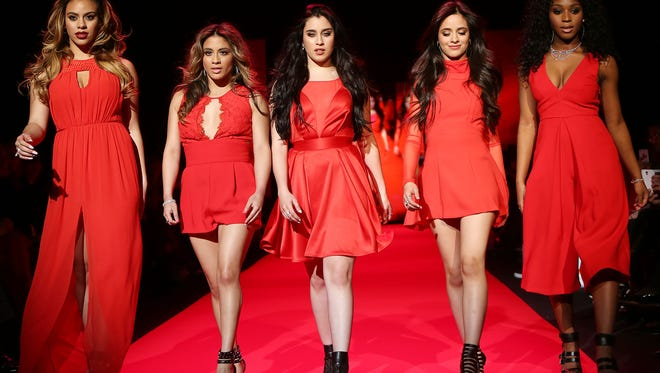 Members of Fifth Harmony, from left, Dinah Jane Hansen, Ally Brooke, Lauren Jauregui, Camila Cabello and Normani Hamilton walk the runway at the Go Red for Women Red Dress Fashion Show at Lincoln Center in New York. (AP Photo/Starpix, Kristina Bumphrey)