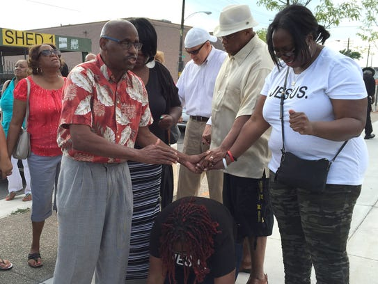 Several people pray over one of two women who were