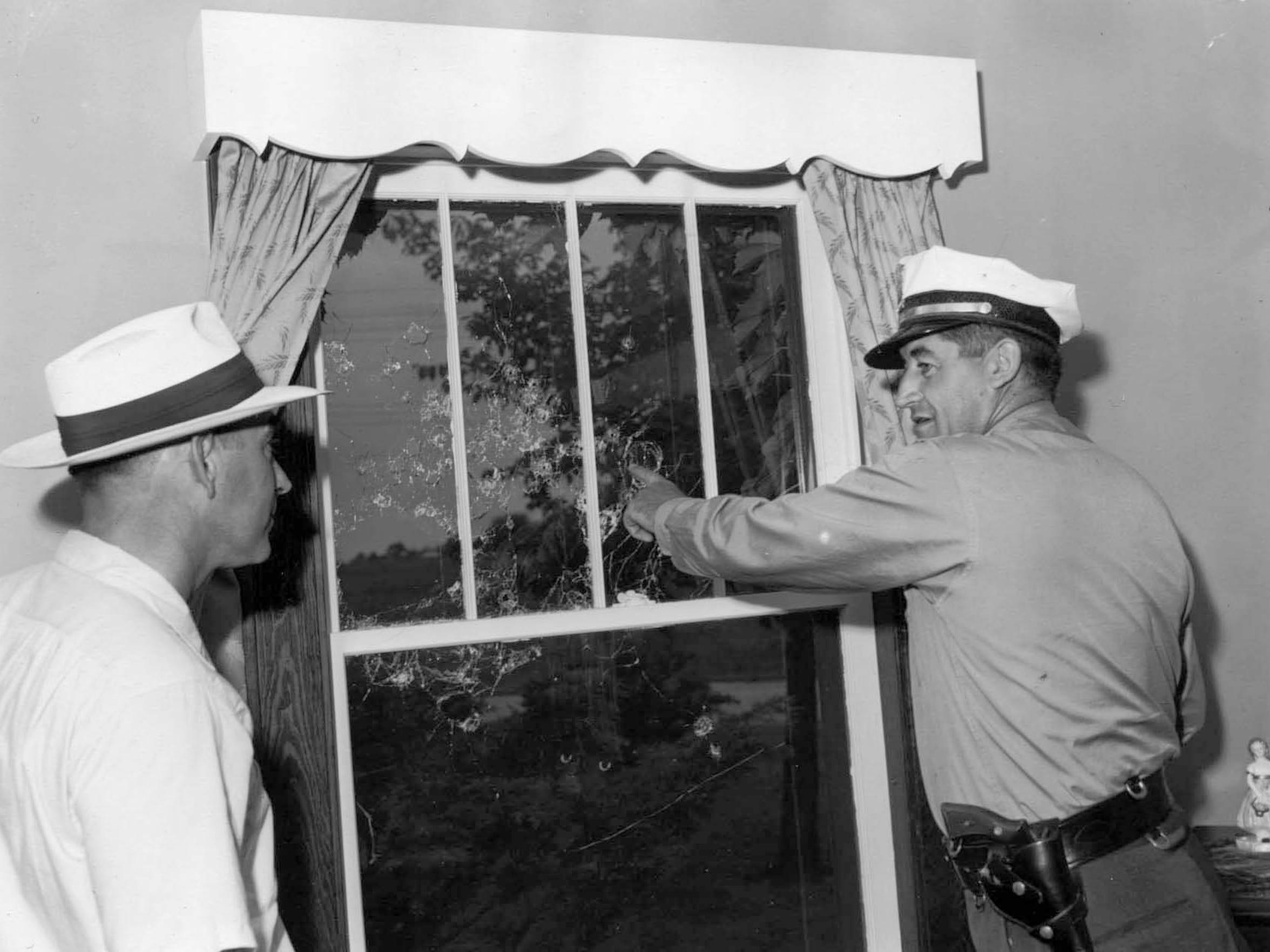 6-29-1954Shotgun blast window at Harold J. curtis, R3 Sheboygan and under Sheriff Lawrence Schmitz look over the damage.
