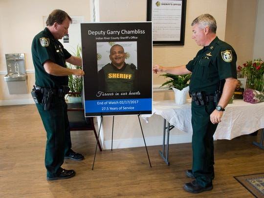 """""""He was beloved by people at work and throughout the community.  He was a mentor for many of our deputies,"""" said Major Selby Strickland (left), who puts up a portrait of Garry Chambliss, with Captain Ryan Haffield (right)  on Saturday, Feb. 18, 2017, in the lobby of the Indian River County Jail in Vero Beach. The pair worked with Chambliss, a corrections deputy for the Indian River County Sheriff's Office, who was shot and killed while off-duty Friday night in the 4400 block of 28th Ave. in Gifford.  A small memorial with photos, cards and flowers was set up in the lobby of the jail, which is open 24 hours a day. Members of the public are welcome to leave flowers and cards.  The sheriff's office will give items left at the memorial to the Chambliss family. To see more photos, go to TCPalm.com."""