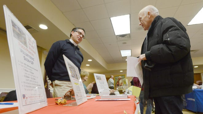 The Church of the Holy Spirit Food Pantry's Rev. Jerry Raccioppi discusses his efforts with Richard Aloia at the second annual open house for networking and recruiting volunteers. The event, hosted by Sustainable Verona and the township, attracts about 100 visitors to 28 local organizations in the Verona Community Center Ballroom, on Tuesday night, Jan. 24.