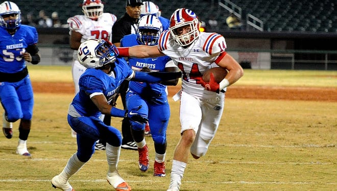 Tanner Ash (14) stiff arms a defensive player in a game earlier this season.