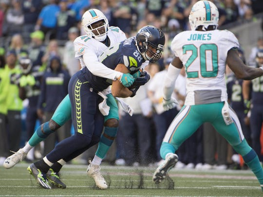 Seattle Seahawks tight end Jimmy Graham (88) picks up a first down as he is tackled by Miami Dolphins defensive back Byron Maxwell (41) during the fourth quarter at CenturyLink Field.