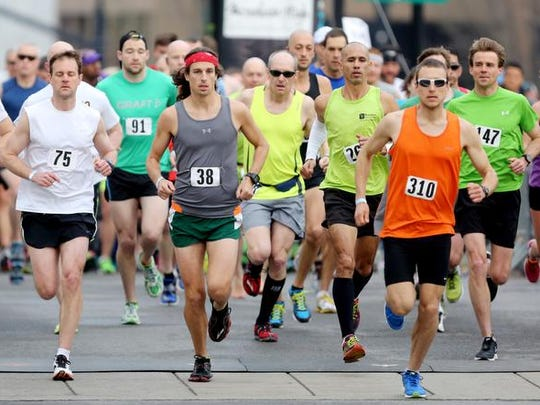 Half marathon runners cross the starting line on Third Avenue for the Music City Half Marathon and 10K.