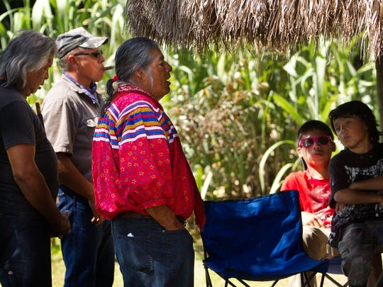Traditional Seminole tribe native, Bobby C. Billie, right,  and Miccosukee natives, Cecil Osceola, left, and Steve Tigertail, back, share native traditions in history with Miccosukee children on an island used for education and cultural purposes.